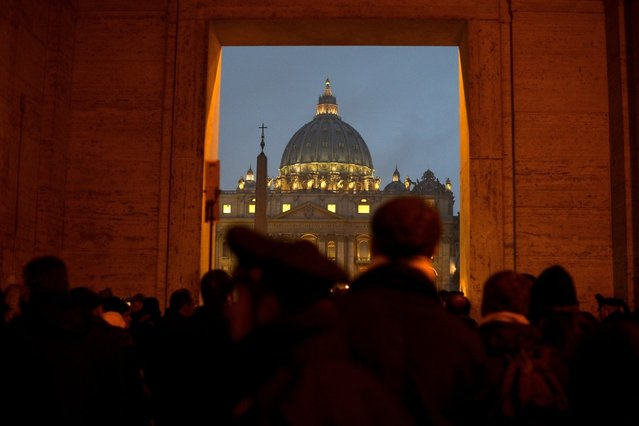 People gather in front of Saint Peter's dome at the Vatican on February 11, 2013 after Pope Benedict XVI announced he will resign as leader of the world's 1.1 billion Catholics on February 28 because his age prevented him from carrying out his duties – an unprecedented move in the modern history of the Catholic Church. (Photo by Filippo Monteforte/AFP Photo)