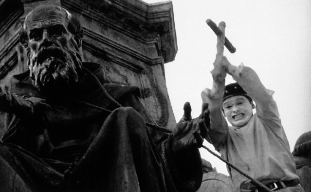A protestor uses a bronze cross pried from the Christopher Columbus statue in Mexico City to pound on one of the monks at the base of the statue, October 12, 1992. An angry mob painted, threw eggs, and pried parts from the statue in protest of the 500th anniversary of Columbus' landing in the Americas. (Photo by Damian Dovarganes/AP Photo)