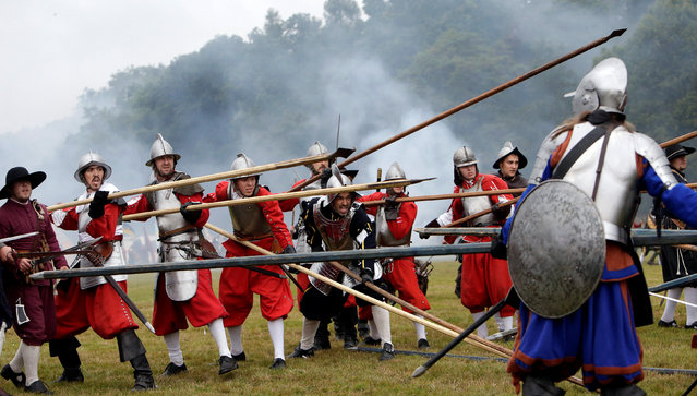 """Participants wearing medieval costumes re-enact the 1620 battle of Bila Hora (Battle of White Mountain) between Bohemian Estates and Austrian Imperial with Catholic forces in Prague, Czech Republic September 18, 2016. The Battle of White Mountain was an early battle in the Thirty Years' War fought on 8 November 1620 (New Style calendar), in which an army of 15,000 Bohemians and mercenaries under Christian of Anhalt were defeated by 27,000 men of the combined armies of Ferdinand II, Holy Roman Emperor, under Charles Bonaventure de Longueval, Count of Bucquoy and the German Catholic League under Johann Tserclaes, Count of Tilly at Bílá Hora (""""White Mountain""""), near Prague (now part of the city). The battle marked the end of the Bohemian period of the Thirty Years' War and decisively influenced the fate of the Czech lands for the next 300 years. (Photo by David W. Cerny/Reuters)"""