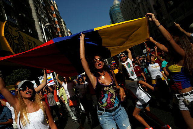 Protesters hold a Venezuelan flag during a demonstration to demand a referendum to remove Venezuela's President Nicolas Maduro, in Madrid, Spain September 4, 2016. (Photo by Susana Vera/Reuters)