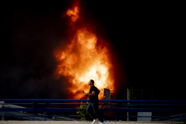A journalist runs past as firefighters work to extinguish a fire at warehouses at the seaport in Beirut, Lebanon, Thursday, September 10. 2020. A huge fire has broken out at the Port of Beirut, sending up a thick column of black smoke and raising new panic among traumatized residents after last month's catastrophic blast at the same site killed nearly 200 people. (Photo by Hassan Ammar/AP Photo)