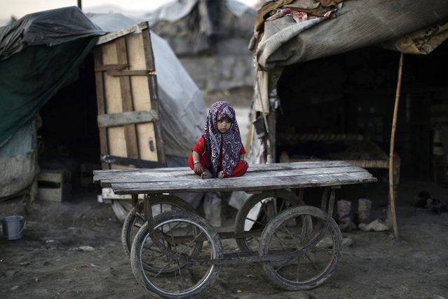 A Pakistani child, whose family was displaced by 2010 floods from a village in Pakistan's Sindh province, sits on a wooden cart outside her family's makeshift home, in a slum on the outskirts of Islamabad, Pakistan, Friday, February 8, 2013. (Photo by Muhammed Muheisen/AP Photo)