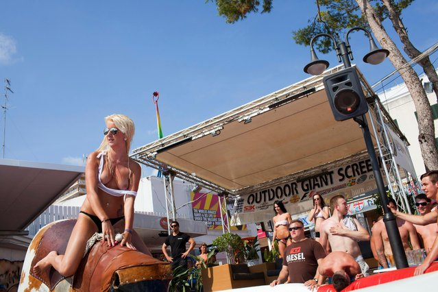 A participant rides the bucking bronco as part of a wet t-shirt competition hosted at Mamboís Terrace, Magaluf, Majorca on June 28, 2013. The competition included women from the British counties of Essex, Stafford and Yorkshire. The competition was eventually won by Monica, from Romania, who received the £100 cash prize. (Photo by Peter Dench/Getty Images Reportage)