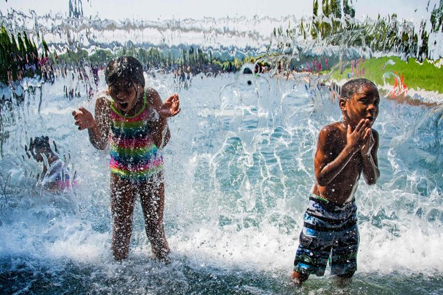 Children play in the waterfall, July 25, 2016, at The Yard Park in Washington DC, as a heat wave rolls across the area. (Photo by Jim Watson/AFP Photo)