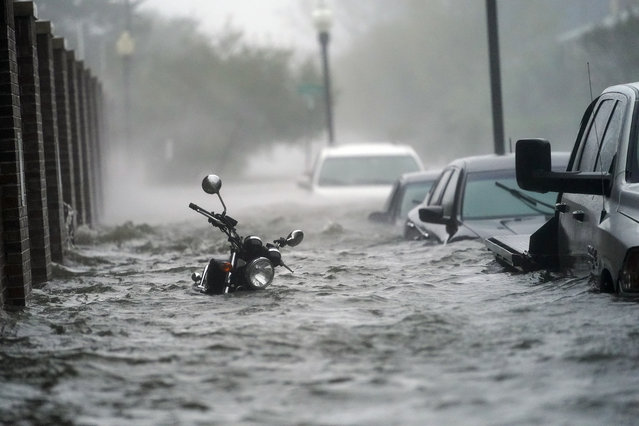 Cars and a motorcycle are underwater as water floods a street, Wednesday, September 16, 2020, in Pensacola, Fla. (Photo by Gerald Herber/AP Photo)