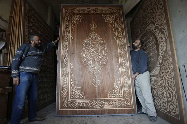 Artist Riad Al Radi (R), a Syrian refugee, and Egyptian carpenter Aref Ramadan show a cover from the giant Koran made entirely of wood in Irbid city, north of Amman November 18, 2014. Al Radi started the project in 2005 back in Syria, but progress was interrupted by the country's civil war. (Photo by Muhammad Hamed/Reuters)