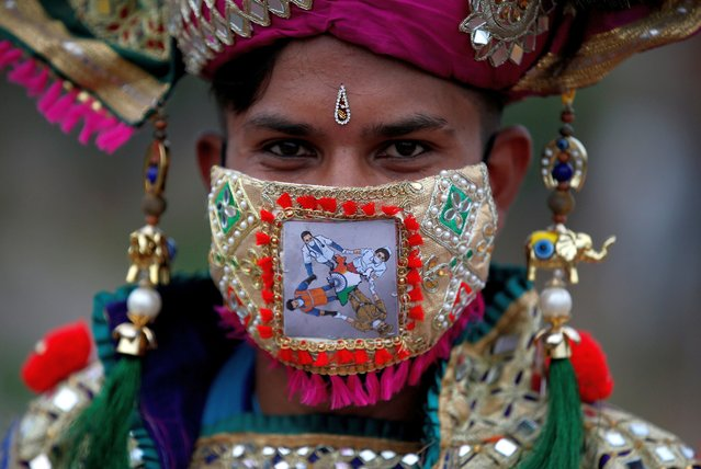 "A participant in traditional costume wearing a mask featuring ""COVID-19 warriors"" as he attends a rehearsal for Garba, a folk dance, ahead of Navratri, a festival during which devotees worship the Hindu goddess Durga and youths dance in traditional costumes, amidst the coronavirus disease outbreak, in Ahmedabad, India, September 18, 2020. (Photo by Amit Dave/Reuters)"