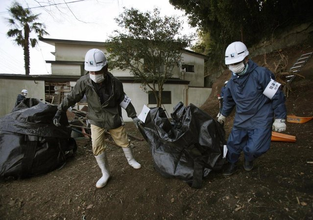 Workers haul a bag of leaves and soil contaminated by radiation, during a clean up operation in the town of Naraha, which was previously inside the exclusion zone surrounding the Fukushima Dai-ichi nuclear plant, in Japan, Wednesday, March 6, 2013.  On March 11, Japan marks two years since an earthquake and tsunami caused the plant to spew radiation into the air, contaminating a large area surrounding it. Decontamination operations continue in areas outside the zone, though few residents have returned to the town since it was re-opened. (Photo by Greg Baker/AP Photo)