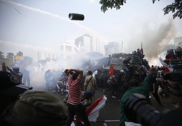 Indonesian police use tear gas and water cannon to disperse supporters of presidential candidate Prabowo Subianto in Jakarta in this August 21, 2014 file photo. After Prabowo supporters had been taunting the police who were holding the barricade, the police launched a very quick and violent strike to disperse them. I had a helmet on so I was able to stand my ground for a few seconds while sticks, rocks and teargas flew through the air – added to that I had attack dogs right behind me. (Photo and caption by Darren Whiteside/Reuters)