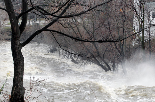 Ellicott Creek rages on Mill St. Tuesday, November 25, 2014, in Amherst, N.Y. The creek has crested to flood stage Tuesday. Authorities on Tuesday kept an eye on rising creek levels a week after the region was hit by record-breaking lake-effect storms. (Photo by Gary Wiepert/AP Photo)