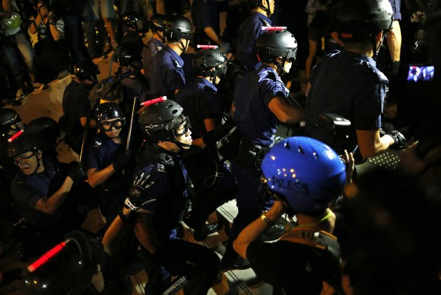Policemen wearing protective gear walk up a flight of stairs as pro-democracy protesters rally close to the chief executive office in Hong Kong, November 30, 2014. (Photo by Tyrone Siu/Reuters)