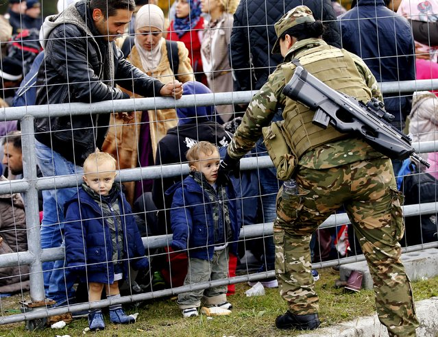 A member of the Slovenian army talks to migrants waiting at the Austrian border near the village of Sentilj, Slovenia, October 25, 2015. Slovenia called on the European Union to take immediate action to stem the flow of refugees and migrants into the 28-member bloc as thousands more arrived in the small Alpine country on Sunday. (Photo by Leonhard Foeger/Reuters)