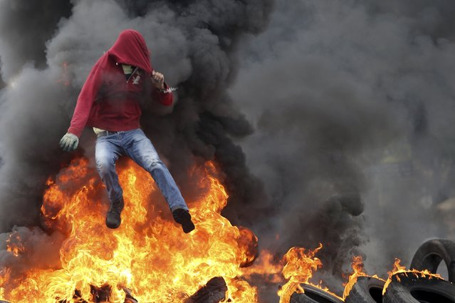A Palestinian protester jumps over burning tyres during clashes with Israeli troops near the Jewish settlement of Bet El, near the West Bank city of Ramallah October 26, 2015. Prime Minister Benjamin Netanyahu has raised the possibility of revoking benefits and travel rights of some Palestinians living in East Jerusalem, a government official said on Monday, in response to a wave of Palestinian violence. (Photo by Mohamad Torokman/Reuters)