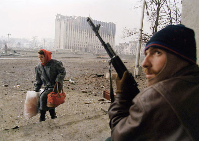 A Chechen fighter opposite the presidential palace, in background, keeps an eye out for snipers as a refugee makes her way across the main square out of harm's way on Tuesday, January 10, 1995 in Grozny. A ceasefire called by the Russian government for the next-48-hours quickly collapsed Tuesday as heavy shelling and small-arms fire again filled the Chechen capital. (Photo by David Brauchli/AP Photo)