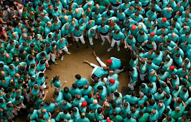 A Casteller de Vilafranca is attended to after falling down from a Castell during a biannual competition in Tarragona city, Spain, October 2, 2016. (Photo by Albert Gea/Reuters)