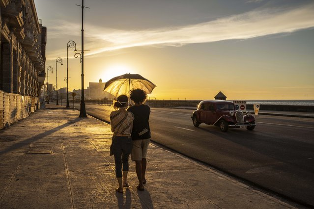 A couple wearing masks as a precaution against the spread of the new coronavirus walk on the Malecon seawall at sunset in Havana, Cuba, Monday, August 31, 2020. Cuban authorities will introduce new measures starting tomorrow Tuesday aimed at containing the spread of the coronavirus in Havana among others a curfew from 7 pm until 5 am and no one without special permission will be able to enter or leave the province. The new measures will last at least 15 days. (Photo by Ramon Espinosa/AP Photo)