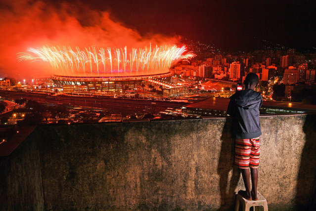 A boy from Mangueira favela watch fireworks over Maracana Stadium during the 2016 Olympics closing ceremony in Rio de Janeiro on August 21, 2016. (Photo by Carl De Souza/AFP Photo)