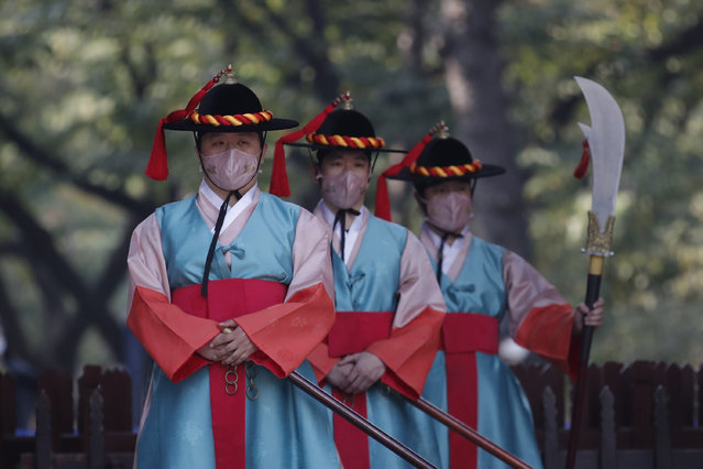 Performers wearing traditional guard uniforms and protective face masks as a precaution against the coronavirus, stand during a re-enactment ceremony of the changing of the Royal Guards, in front of the main gate of the Deoksu Palace, one of South Korea's well-known landmarks, in downtown Seoul, South Korea, Tuesday, October 20, 2020. (Photo by Lee Jin-man/AP Photo)