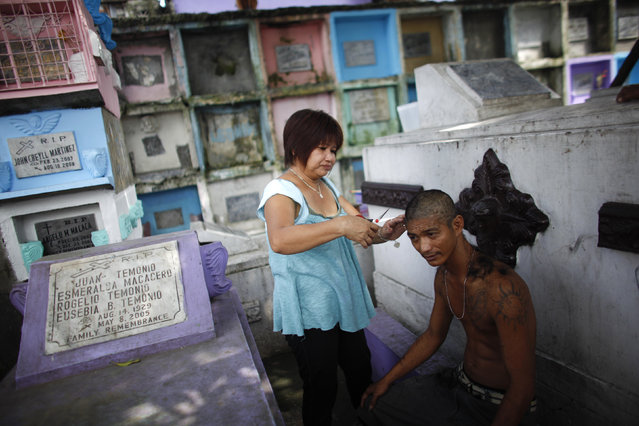 """A resident gets a haircut in front of """"apartment-style"""" tombs inside the Manila North Cemetery, October 28, 2011. (Photo by John Javellana/Reuters)"""