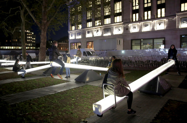 Visitors interact with a light up seesaw installation in London, Britain October 5, 2016. (Photo by Neil Hall/Reuters)