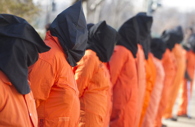 Protestors wear orange prison jumpsuits and black hoods on their heads during protests against holding detainees at the military prison in Guantanamo Bay during a demonstration on Capitol Hill in Washington, D.C., on January 8, 2013. (Photo by Saul Loeb/AFP Photo /The Atlantic)