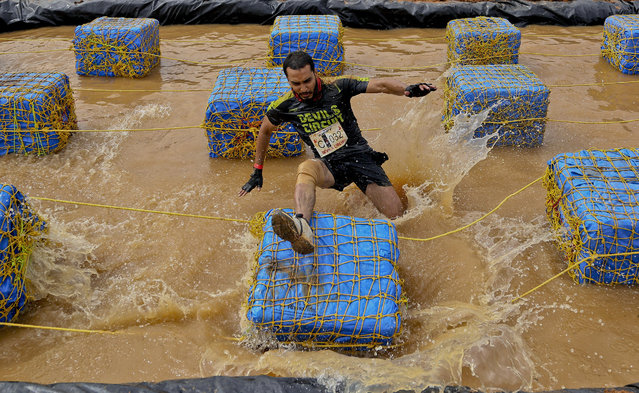 A participant loses his balance while attempting to cross an obstacle during Devils Circuit, an obstacle run event in Bangalore, India, Sunday, November 1, 2015. More than 3,000 contestants participated in the event. (Photo by Aijaz Rahi/AP Photo)
