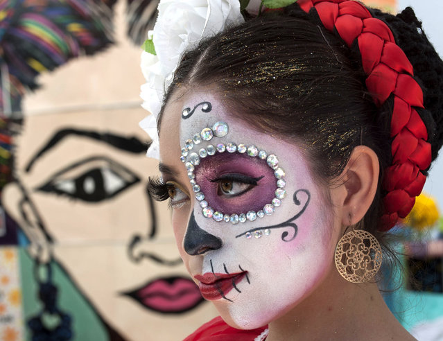 "Mary Triana, 16, wears an intricate Day Of The Dead face at the first annual ""Viva la Vida"" festival at the Santa Ana, Calif., train station Sunday, November 1, 2015. (Photo by Ana Venegas/The Orange County Register via AP Photo)"