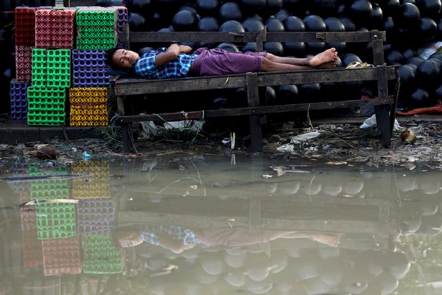 A man sleeps on a bench along a flooded street in Yangon in this September 30, 2015 file photo. (Photo by Soe Zeya Tun/Reuters)