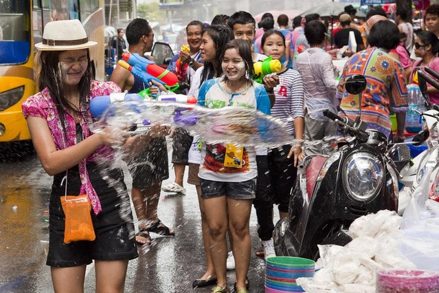 A woman reacts to being soaked by water during a community water fight as part of the Songkran water festival on April 14, 2013 in Bangkok, Thailand. The Songkran festival marks the traditional Thai New Year and is celebrated each year from April 13 to 15. The throwing of water originated as a way to pay respect to people and is meant as a symbol of cleansing and purification. (Photo by Jack Kurtz)