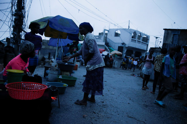 People buy goods on the street while Hurricane Matthew approaches Port-au-Prince, Haiti, October 3, 2016. (Photo by Carlos Garcia Rawlins/Reuters)