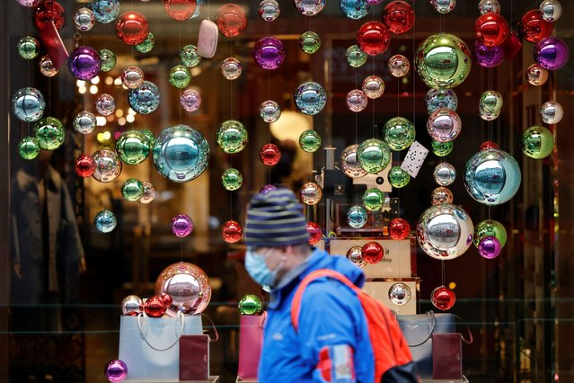 People walk in the rain past Christmas decorations in central London on November 20, 2020, as life under a second lockdown continues in England. The current lockdown in England has shuttered restaurants, gyms and non-essential shops and services until December 2, with hopes business could resume in time for Christmas. (Photo by Tolga Akmen/AFP Photo)