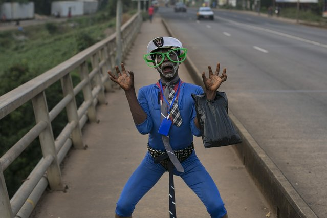 A Sierra Leonean man in costume poses on a street in Freetown, Sierra Leone, December 16, 2014. (Photo by Baz Ratner/Reuters)