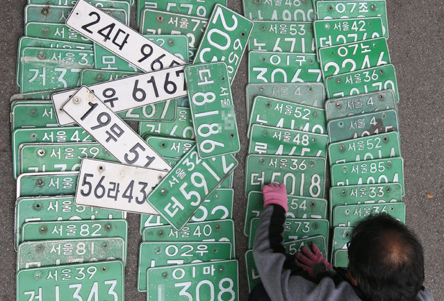 An employee at Jongno Ward Office sorts through confiscated car license plates in Seoul, South Korea, 12 November 2015. The plates were taken from cars owned by people who repeatedly dodged paying taxes in a campaign conducted nationwide. (Photo by EPA/Yonhap)