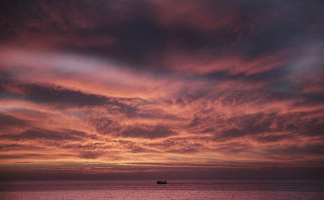 A Palestinian fishing boat sails as the sun sets on the coast off Gaza City, Sunday, March 18, 2018. (Photo by Khalil Hamra/AP Photo)