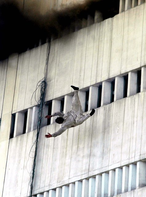 The man falls from the fifth floor of the 13-story building. (Photo by K.M. Chaudary/Associated Press)