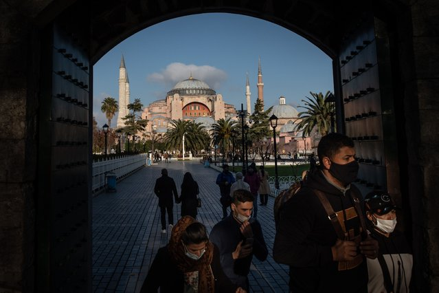 Tourists enter the grounds of the Blue mosque in front of the Hagia Sophia Grand Mosque during a national weekend coronavirus lockdown on December 06, 2020, in Istanbul, Turkey. Amid surging coronavirus figures, Turkey has reimposed weekday curfews and full weekend lockdowns with the exception of tourists to curb the spread of the virus. (Photo by Chris McGrath/Getty Images)