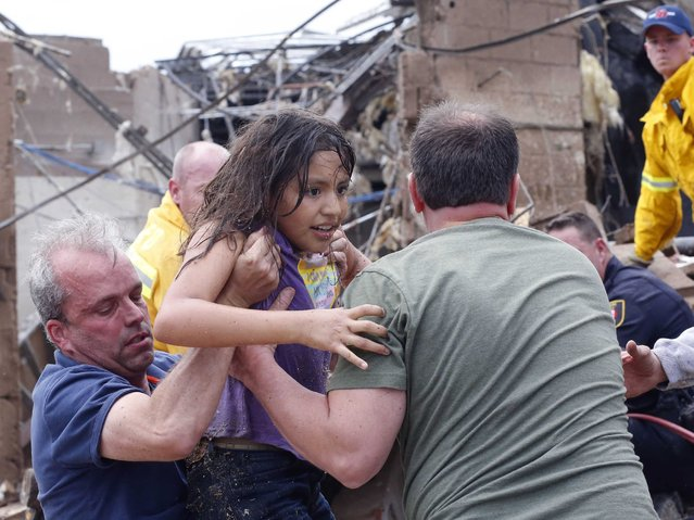 A child is pulled from the rubble of the Plaza Towers Elementary School in Moore, Okla., and passed along to rescuers Monday, May 20, 2013. (Photo by Sue Ogrocki/AP Photo)