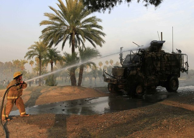 An Afghan firefighter sprays water on a U.S. armoured vehicle after a suicide attack on the outskirts of Jalalabad, January 5, 2015. (Photo by Reuters/Parwiz)