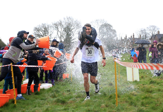 Mark Threlfall and Cassie Yates compete in the annual wife-carrying race in Dorking, England on March 1, 2020. (Photo by Rex Features/Shutterstock)