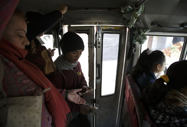 Suraj Shrestha (C), the conductor of a women-only bus, collects the bus fare from a passenger in Kathmandu January 6, 2015. (Photo by Navesh Chitrakar/Reuters)