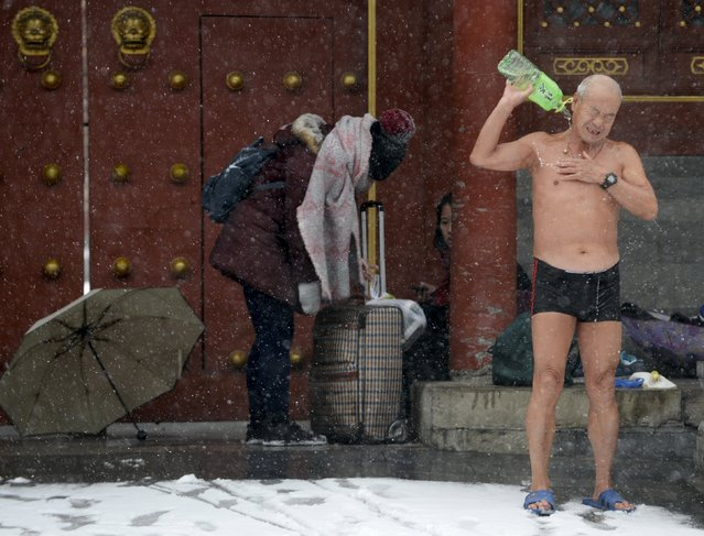 A winter swimmer pours water on his body to clean up after swimming in the Shichahai Lake amid heavy snowfall in Beijing, China, November 22, 2015. Snowstorms have swept across a vast area of north China, disrupting traffic, grounding flights and slowing bullet trains in Beijing, Tianjin, Hebei Province and the Inner Mongolia Autonomous Region, Xinhua News Agency reported. (Photo by Reuters/Stringer)
