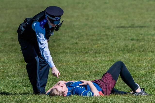 Police officers speak to a woman in Greenwich Park in London, England on April 4, 2020. The Government has announced a lockdown to slow the spread of Coronavirus and reduce pressure on the NHS. (Photo by Alamy Live News)