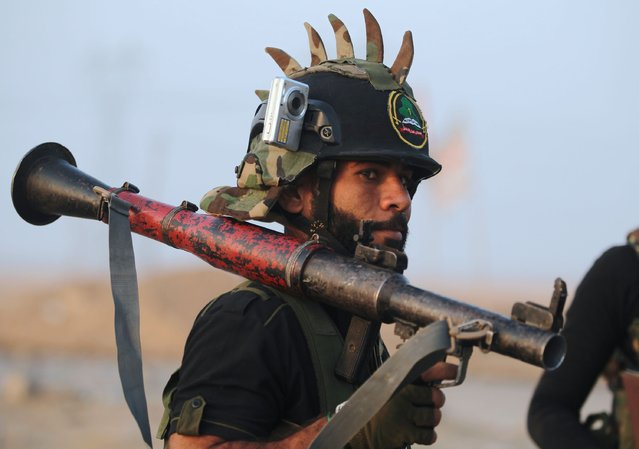 A Shiite fighter from the Hashed al-Shaabi (Popular Mobilisation) patrols in the village of Ayn Nasir, south of Mosul, on October 29, 2016, after recapturing it from Islamic State group jihadists in an ongoing operation to retake the city of Mosul. Iraqi paramilitary forces launched an operation to cut the Islamic State group's supply lines between its Mosul bastion and neighbouring Syria, opening a new front in the nearly two-week-old offensive. (Photo by Ahmad Al-Rubaye/AFP Photo)