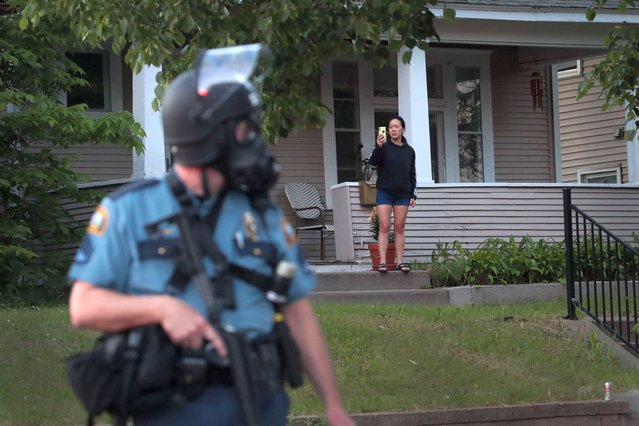 """A police officer keeps watch during a protest as a woman looks on May 28, 2020 in St. Paul, Minnesota. Today marks the third day of ongoing protests after the police killing of George Floyd. Four Minneapolis police officers have been fired after a video taken by a bystander was posted on social media showing Floyd's neck being pinned to the ground by an officer as he repeatedly said, """"I can't breathel"""". Floyd was later pronounced dead while in police custody after being transported to Hennepin County Medical Center. (Photo by Scott Olson/Getty Images)"""