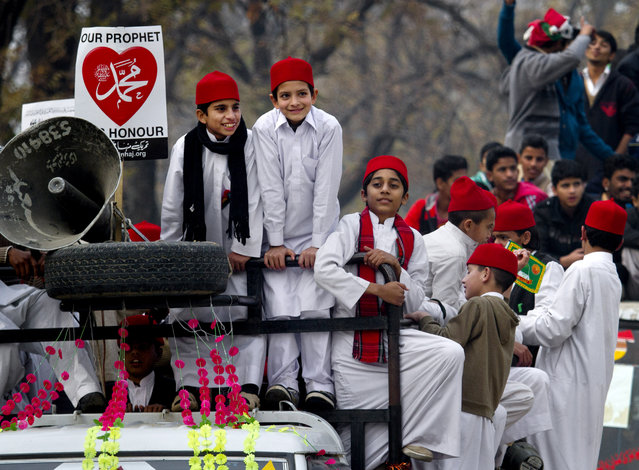 Pakistani boys take part in a rally marking the birthday of Islam's Prophet Muhammad in Islamabad, Pakistan, Sunday, January 4, 2015. Thousands of Pakistani Muslims celebrated by participating in religious ceremonies and distributing free meals for the poor. (Photo by Anjum Naveed/AP Photo)