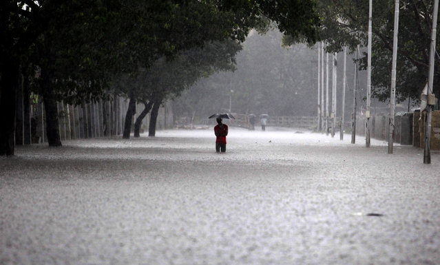 An Indian man shelters under an umbrella as he walks through floodwaters in Chennai on December 1, 2015, during a downpour of heavy rain in the southern Indian city.  Heavy rains pounded several parts of the southern Indian state of Tamil Nadu and inundating most areas of Chennai, severely disrupting flights, train and bus services and forcing the postponment of half-yearly school exams. (Photo by AFP Photo/Stringer)