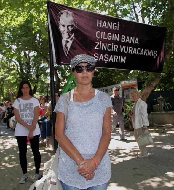 "Turks stand in a silent protest in Kugulu Park in Ankara, Turkey, Wednesday, June 19, 2013. After weeks of sometimes-violent confrontation with police, Turkish protesters have found a new form of resistance: standing still and silent. The banner with an image of Turkey's founder Kemal Ataturk reads: ""Which crazy person thinks they can put me in chains"". (Photo by Burhan Ozbilic/AP Photoi)"