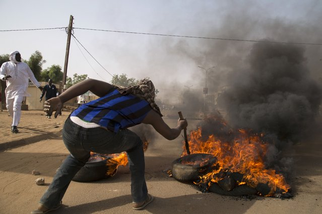 A man burns a tire during a protest against Niger President Mahamadou Issoufou's attendance last week at a Paris rally in support of French satirical weekly Charlie Hebdo, which featured a cartoon of the Prophet Mohammad as the cover of its first edition since an attack by Islamist gunmen, in Niamey January 17, 2015. (Photo by Tagaza Djibo/Reuters)