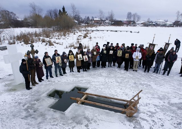 People attend an Orthodox religious service during a water blessing ceremony on Epiphany Day in the village of Velikoye, Yaroslavl region, January 18, 2015. Orthodox believers mark Epiphany on January 19 by immersing themselves in icy waters regardless of the weather. (Photo by Sergei Karpukhin/Reuters)