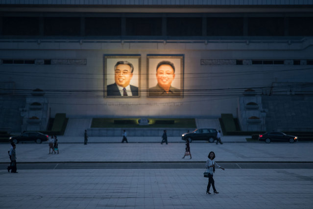 Pedestrians make their way past the portraits of late North Korean leaders Kim Il Sung (L) and Kim Jong Il (R) displayed in Kim Il Sung square in central Pyongyang on June 12, 2018. (Photo by Ed Jones/AFP Photo)